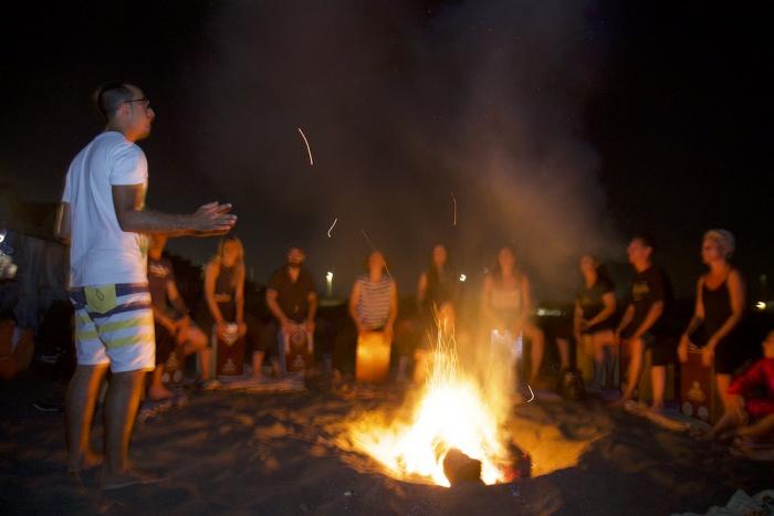 Attilio Celona e la sua classe di cajon intorno al fuoco, sul mare di ostia.jpg