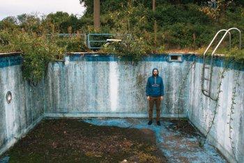 Caso, il suo k-way blu elettrico e una piscina.