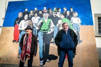 """Mauro Pagani e Francesco Guccini di fronte al murales-copertina di """"Note di viaggio – Capitolo 2"""""""